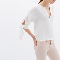 V-NECK TOP WITH KNOTTED SLEEVE