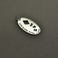 Love is like flying a kite oval brass pendant