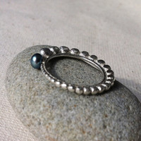 "The ""Round pearl"" ring, topped with a small black pearl river."