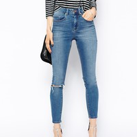 ASOS Ridley High Waist Ultra Skinny Ankle Grazer Jeans in Busted Mid Wash Blue with Ripped Knee at asos.com