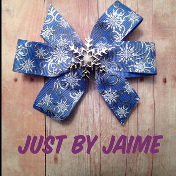 Blue with silver swirls and white snowflakes pinwheel bow on partially lined alligator clip with no slip clip - approx. 4 inches across