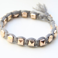 Arm candy - Gold pyramid beads and grey cord - woven bracelet