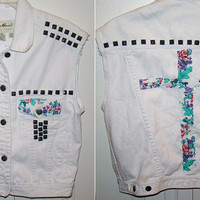 White vest with black studs and floral cross and details