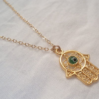 Hamsa and green glass evil eye gold charm on gold filled necklace.