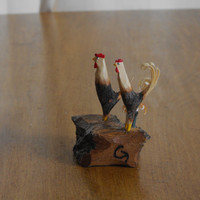 two whittled roosters and a orange flower 0125
