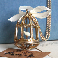 a vintage style golden birdcage necklacewith a cute by Sevinoma