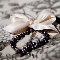 Pale pink fresh water pearls finished with a beautiful black satin bow or Grey/blue fresh water pearls finished with a cream satin bow.   Bracelet has metal chain and lobster clasp for easy removal without compromising the perfect bow.