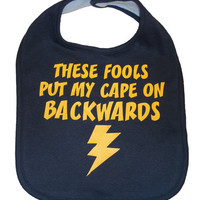 These fools put my cape on backwards baby bib infant toddler funny superhero flash shower gift -  navy blue and yellow