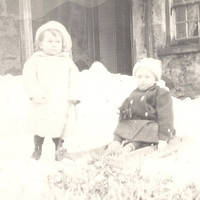 Vintage RPPC Two young children playing in the snow with a sled, AZO stamp box postcard