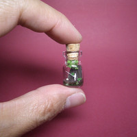 Tiny angler is fishing in the river in a tiny bottle