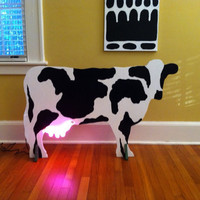 Fabulous wooden cow with pink neon udders by ArdsleyArtGlass
