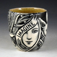 Black and white hand painted cup with ladies, cat, rabbit, house and the word Imagine